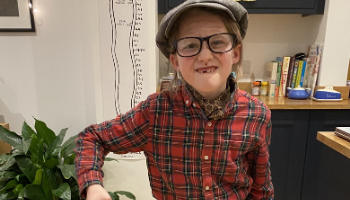 Young girl wears flat cap dressing up as old man